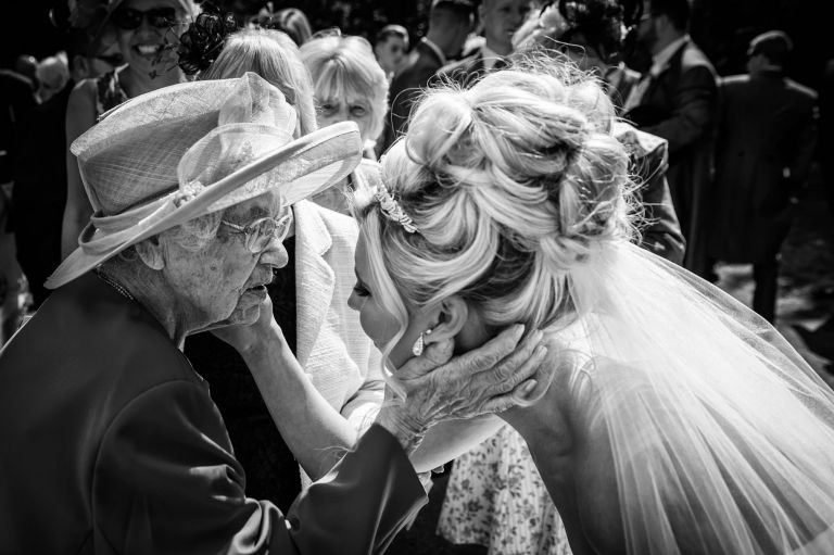 Bride and 104 year old great grandmother touch each others faces at Bray wedding