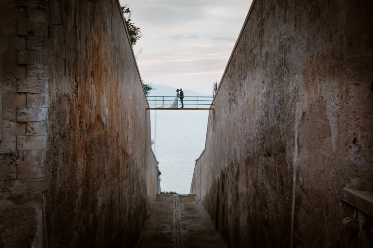 Kissing on the bridge at Cap Rocat by Mallorca wedding photographer Graham Warrellow